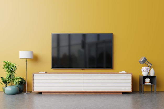 Tv no armário na moderna sala de estar com lâmpada no fundo da parede amarela