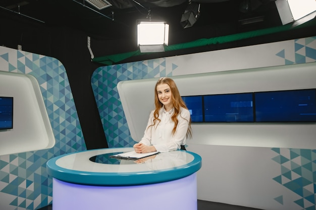 Tv presente em estúdio preparando-se para nova transmissão. menina sorridente na camisa branca, sentada à mesa.