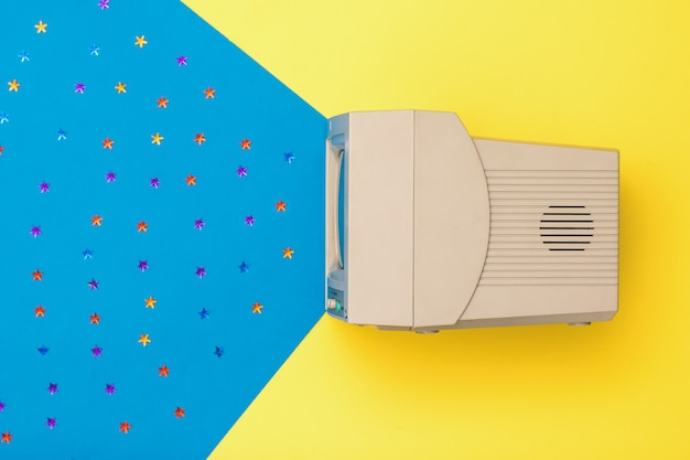 Tv retrô em fundo amarelo e azul. a vista do topo. eletrônica vintage.