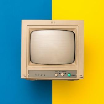 Tv retrô na superfície amarela e azul. a vista do topo. eletrônica vintage.