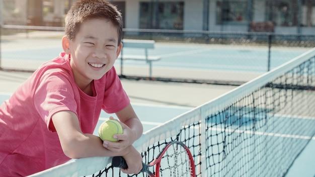 Tween saudável e feliz jovem pré-adolescente misturado jogador de tênis asiático menino iniciante na quadra azul ao ar livre