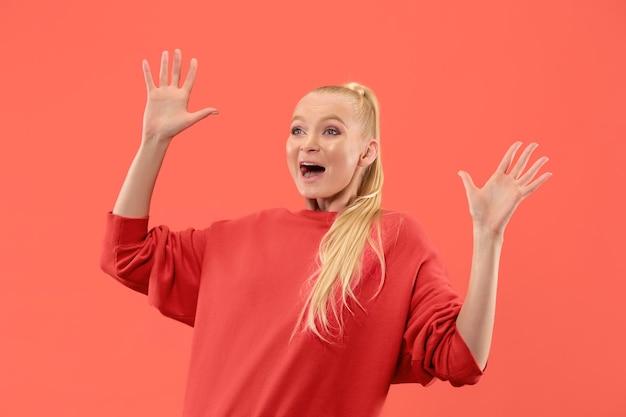 Uau. belo retrato feminino com metade do comprimento frontal isolado no coral studio backgroud. jovem emocional surpresa mulher em pé com a boca aberta. emoções humanas, conceito de expressão facial. cores da moda