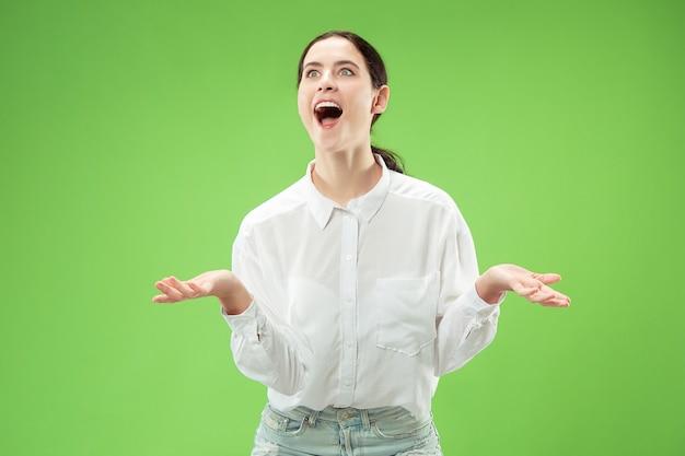 Uau. belo retrato feminino metade frontal isolado no estúdio verde backgroud. jovem mulher surpresa emocional em pé com a boca aberta. emoções humanas, conceito de expressão facial. cores da moda