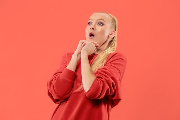 Uau. belo retrato frontal feminino de meio comprimento isolado no coral backgroud. mulher jovem e emocional surpresa em pé com a boca aberta