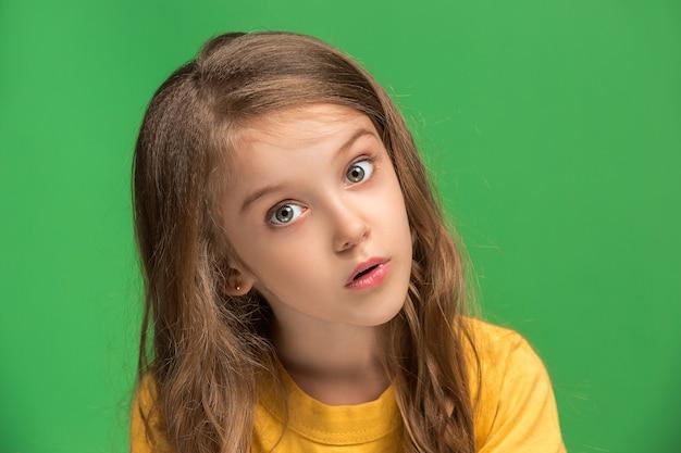 Uau. belo retrato frontal feminino isolado na parede verde. jovem adolescente surpresa emocional em pé com a boca aberta. emoções humanas, conceito de expressão facial.