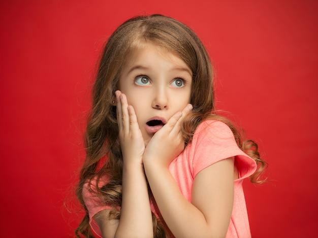 Uau. belo retrato frontal feminino isolado no vermelho studio backgroud. jovem adolescente surpresa emocional em pé com a boca aberta. emoções humanas, conceito de expressão facial. cores da moda