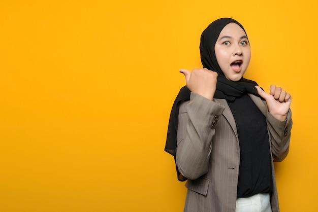 Uau e cara de surpresa de mulher asiática apontando para o espaço vazio
