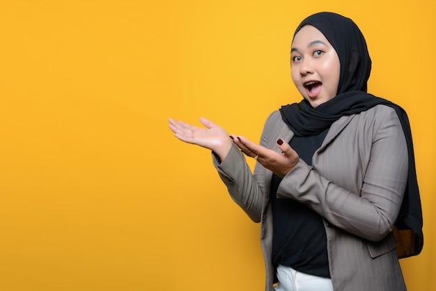 Uau e cara surpresa de mulher asiática mostrando produto