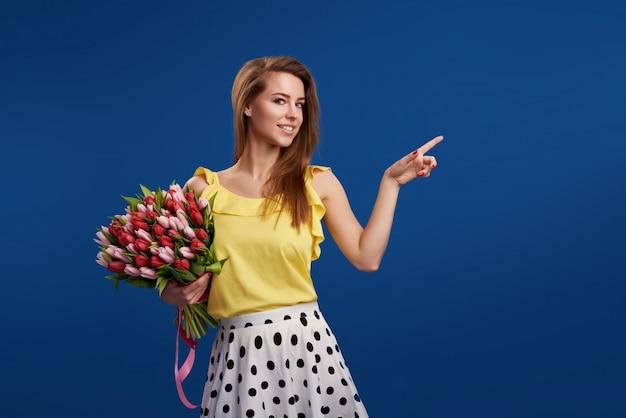 Uau efeito. flores maravilhosas no dia das mulheres. a mulher triguenha de sorriso macia levanta com tulipas brancas, olha felizmente, isolado sobre a parede azul do espaço do estúdio. espaço para texto
