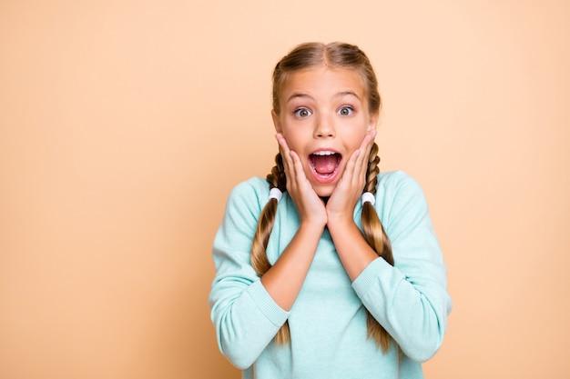 Uau! foto do close up de uma senhora muito bonita de mãos dadas no rosto gritando com os preços de venda fazendo compras com a boca aberta e vestindo um pulôver azul isolado bege