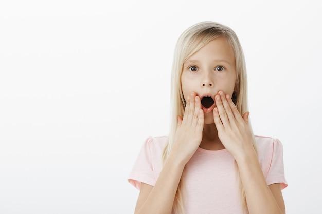 Uau, garoto chocado ao ouvir notícias incríveis sobre o desenho animado favorito. foto interna da filha loira feliz espantada e surpresa, ofegando, em pé com as mãos perto da boca aberta e olhos arregalados, sendo atordoada