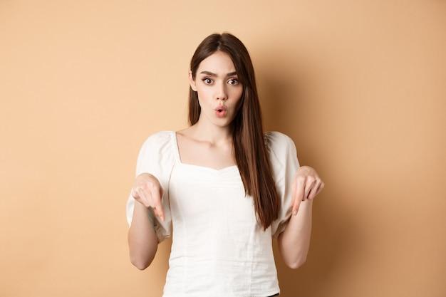Uau incrível. mulher jovem impressionada parece atônita com o produto, apontando o dedo para o logotipo, em pé sobre um fundo bege.