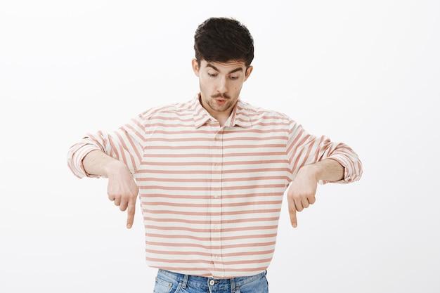 Uau, incrível, olhe para baixo. retrato de um estudante do sexo masculino branco e surpreso com uma camisa listrada, apontando para baixo e assobiando de emoções fascinadas, em pé