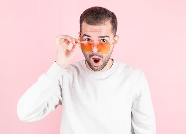 Uau, jovem surpreso com a boca aberta, tocando óculos vermelhos com uma mão.