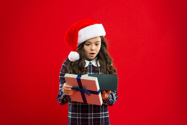 Uau. menina com chapéu de papai noel vermelho. compras de natal. boas férias de inverno. pequena garota surpresa. presente para o natal. infância. festa de ano novo. criança de papai noel. o que.