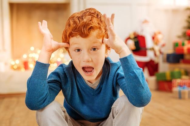 Uau. menino emocional que mantém a boca bem aberta e toca as têmporas enquanto fica animado e não consegue acreditar no que vê.