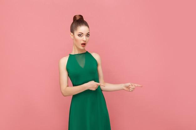 Uau, olhe para cá! mulher apontando o dedo para o espaço da cópia. conceito de emoção e sentimentos de expressão. foto de estúdio, isolada em fundo rosa