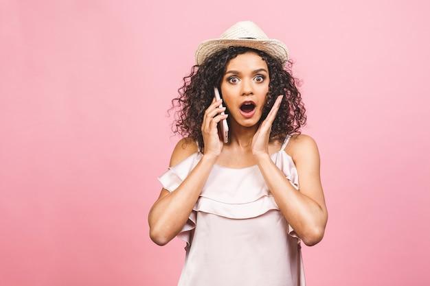 Uau, ótimas notícias! retrato de uma jovem afro-americana chocada em vestido lusing telefone móvel isolado sobre fundo rosa.