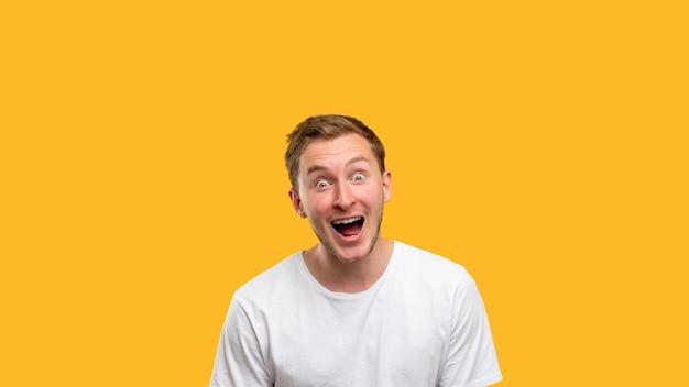 Uau, retrato. experiência comercial. homem animado com a boca aberta, isolada no espaço laranja da cópia.