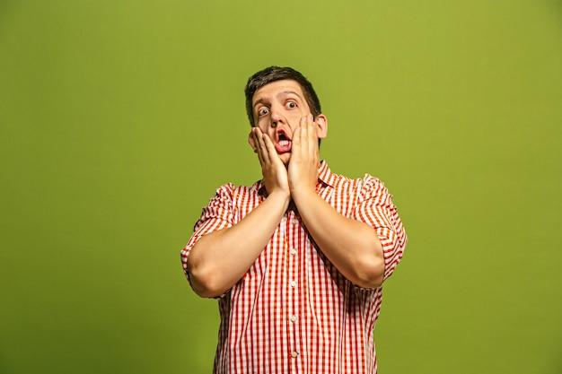 Uau. retrato frontal com metade do comprimento masculino atraente em estúdio verde backgroud. homem barbudo surpreso emocional jovem em pé com a boca aberta. emoções humanas, conceito de expressão facial. cores da moda