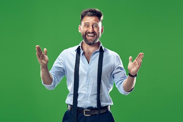 Uau. retrato frontal de homem atraente com metade do corpo em estúdio verde