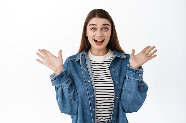 Uau, super incrível. garota feliz surpresa olhando maravilhada, ganhando alguma coisa, batendo palmas e se alegrando, ofegando maravilhada e satisfeita, em pé sobre uma parede branca