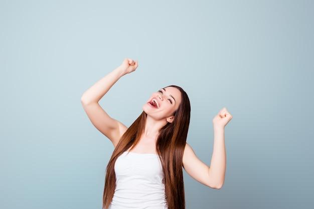 Uau! um sonho da jovem morena bonita se tornou realidade. ela está muito animada, vestindo roupa de verão, comemorando de mãos levantadas, em um espaço azul claro