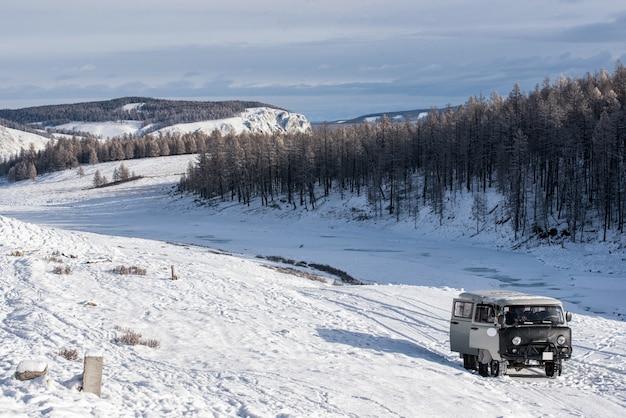 Uaz - van russo na pradaria com montanhas cobertas de neve no fundo na mongólia