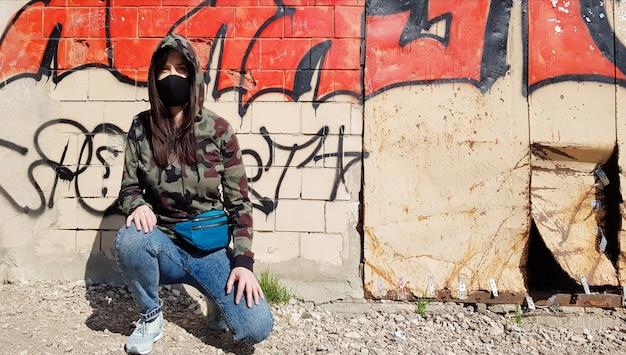 Ucrânia, kiev - 24 de abril de 2020. uma linda mulher com um capuz e uma máscara protetora, vestida de jeans e uma jaqueta de camuflagem cáqui, senta-se perto de uma parede com grafite. na rua.