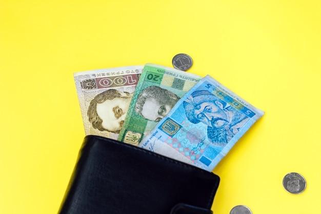 Ucraniano dinheiro pequeno hryvnia e uma moeda em uma carteira de couro preto.