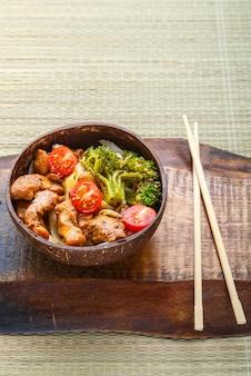 Udon com carne ao molho japonês em um prato de lascas de coco em um carrinho de pauzinhos. foto vertical