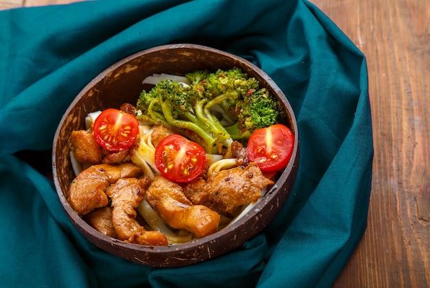 Udon com carne e legumes em molho de yakiniku em um prato de cascas de coco em uma mesa de madeira em um guardanapo azul. foto horizontal