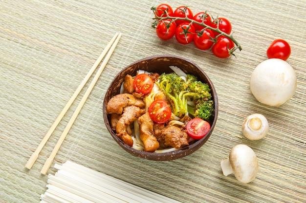 Udon com carne e vegetais ao molho yakiniku em um prato ao lado de pauzinhos e vegetais. foto horizontal