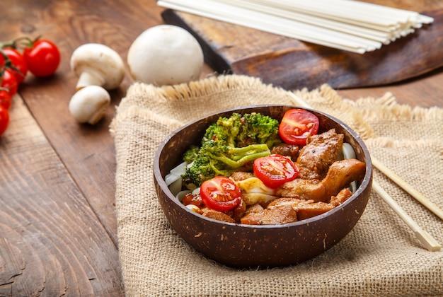 Udon com carne e vegetais ao molho yakiniku em um prato de cascas de coco em um guardanapo de linho ao lado de pauzinhos e vegetais.