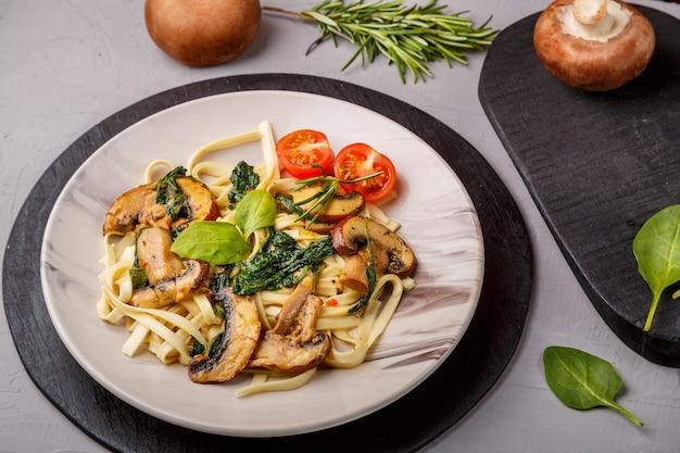 Udon com cogumelos e espinafre em um prato num guardanapo em um fundo de concreto perto de cogumelos e talheres em um quadro negro. foto horizontal