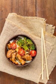 Udon com frango ao molho japonês em um prato de cascas de coco em um guardanapo foto vertical