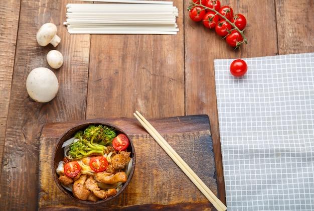 Udon com frango ao molho japonês em um prato de cascas de coco em um suporte de pauzinhos