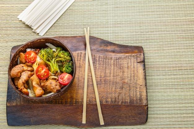Udon de frango ao molho japonês em um prato de lascas de coco em um suporte de pauzinhos foto horizontal