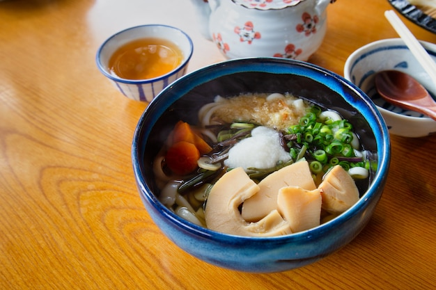 Udon de inverno com chá quente na mesa de madeira.