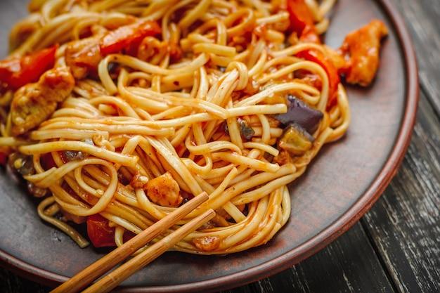 Udon fritar macarrão com carne de frango em molho agridoce na tigela em fundo escuro