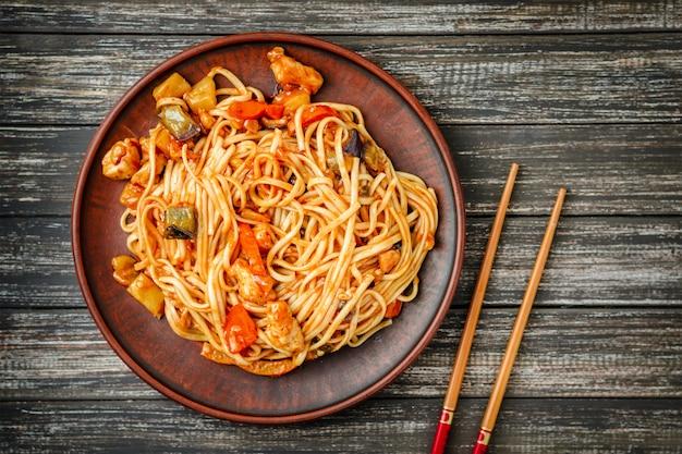 Udon fritar macarrão com frango e molho agridoce e varas de madeira na mesa de madeira