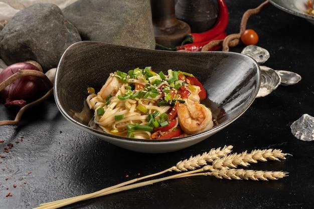 Udon macarrão com camarão e cebolinha em uma mesa de cozinha de pedra preta