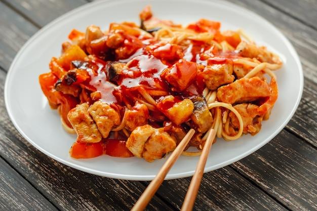 Udon macarrão com frango e legumes em um prato branco close-up