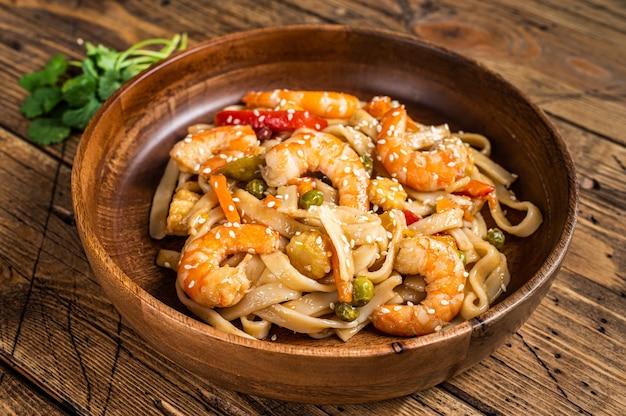 Udon refogado com macarrão de camarão em uma tigela de madeira