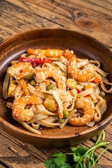 Udon refogado noodles com camarão camarão em uma tigela de madeira. Foto Premium