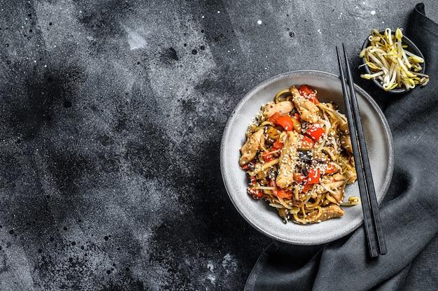 Udon refogado noodles com frango e gergelim