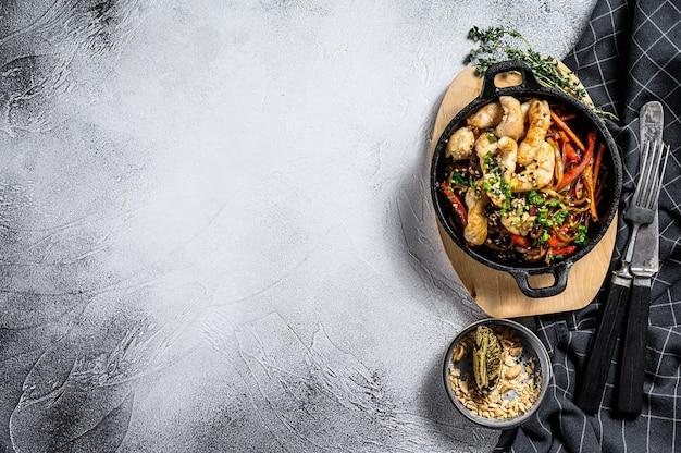 Udon salteado noodles com frango e legumes na panela