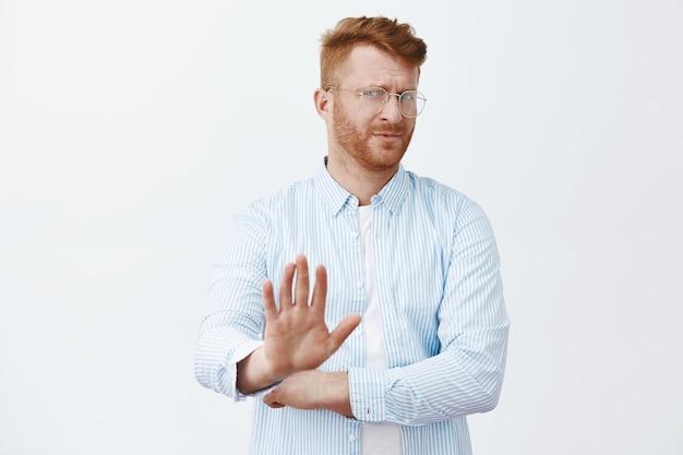 Ufa, não, obrigado, eu passo. desagradado, não impressionado e desinteressado, homem ruivo maduro bonito com barba, virando-se e puxando a palma da mão em um gesto de não, recusando ou recusando a oferta