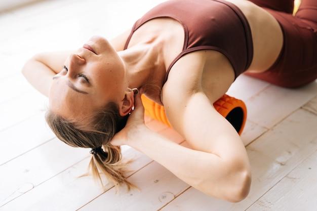 Ufa, rússia - 15 de maio de 2020. close-up de uma jovem com corpo atlético perfeito massageando a fáscia dos músculos das costas e deitada de costas no peitoril da janela no rolo de massagem.