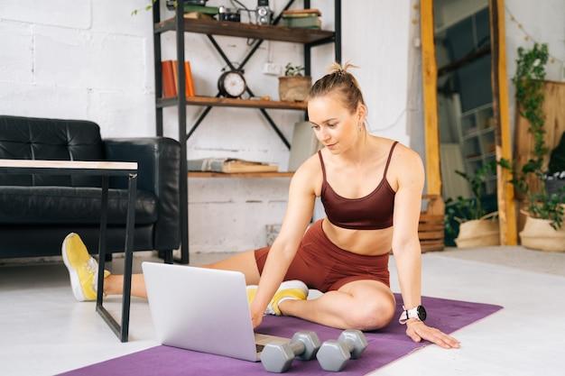 Ufa, rússia - 15 de maio de 2020. esportiva fit jovem com corpo atlético perfeito, vestindo roupas esportivas, assistindo exercícios online no laptop durante o treinamento de treino. conceito de estilo de vida saudável